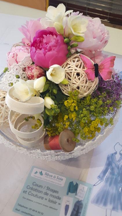 """Bouquet de fleurs roses et feuillage, décoré d'une bobine de fil, d'un papillon rose et d'un ruban couture, avec à côté un croquis de mode et un flyer """"Rêve à Soie""""- vue à l'exposition du club ABC en mai 2017"""