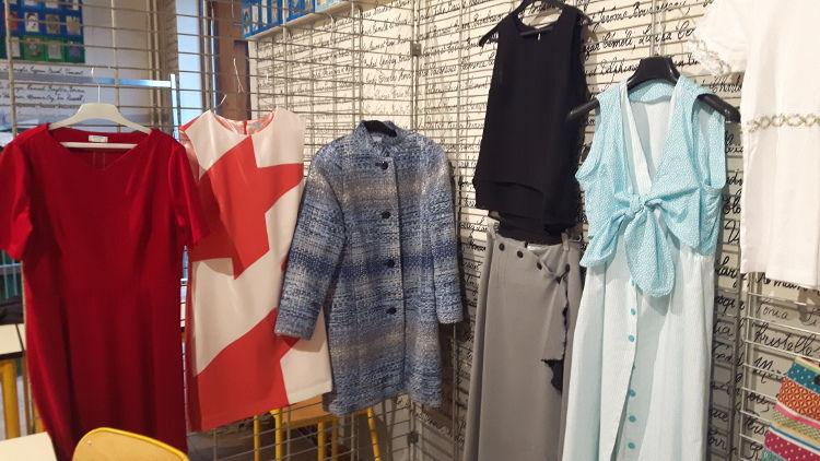 """Stand du cours de """"stylisme - confection femme"""" avec différents modèles réalisés par les élèves suspendus aux grilles (3 robes, 1 manteau, 1 jupe, 1 top)- vue à l'exposition du club ABC en mai 2017"""