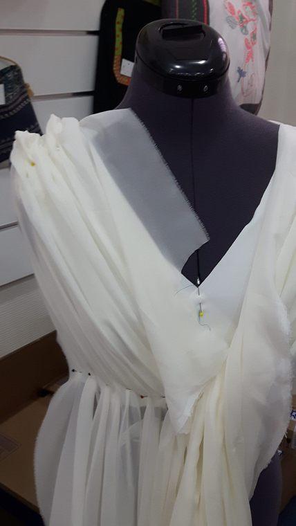 Vue de face du haut d'une robe de mariée, essai de drapé épaule dans la mousseline de la sur-robe le long d'une encolure en V - modèle d'une élève des ateliers Rêve à Soie